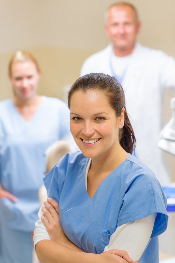 Smiling dental hygienist woman with stomatology team of