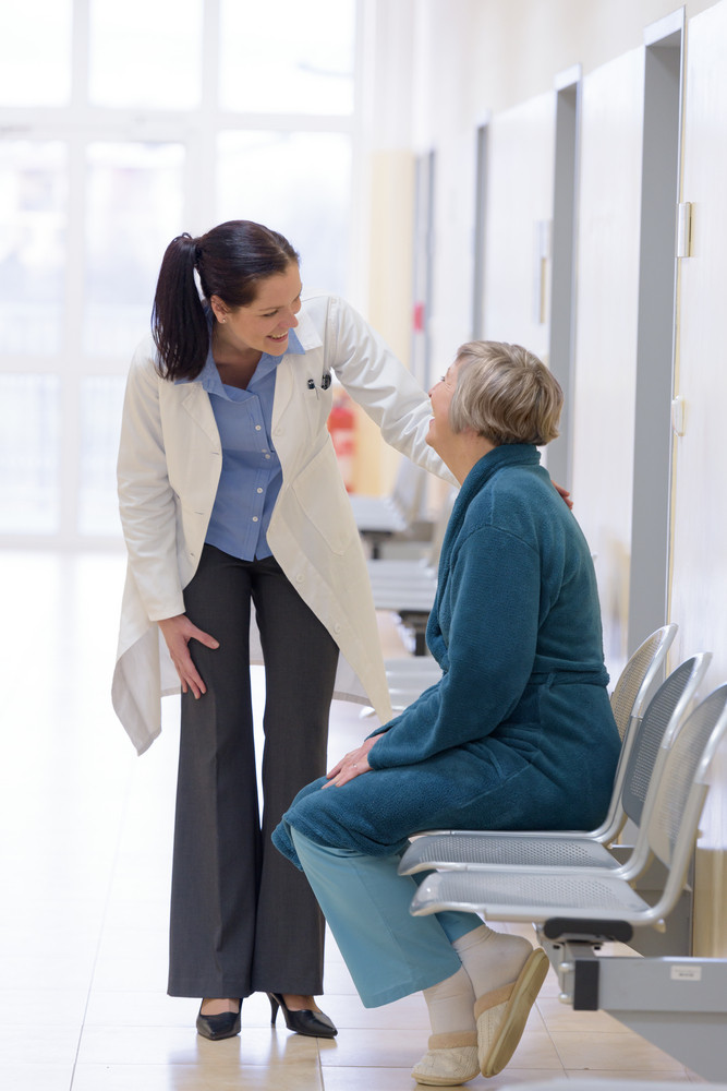 Smiling female doctor smiling with senior patient in hospital corridor