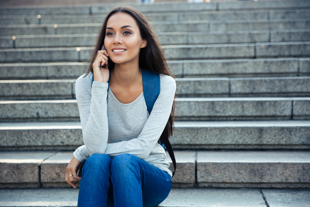 Smiling female student talking on the phone outdoors