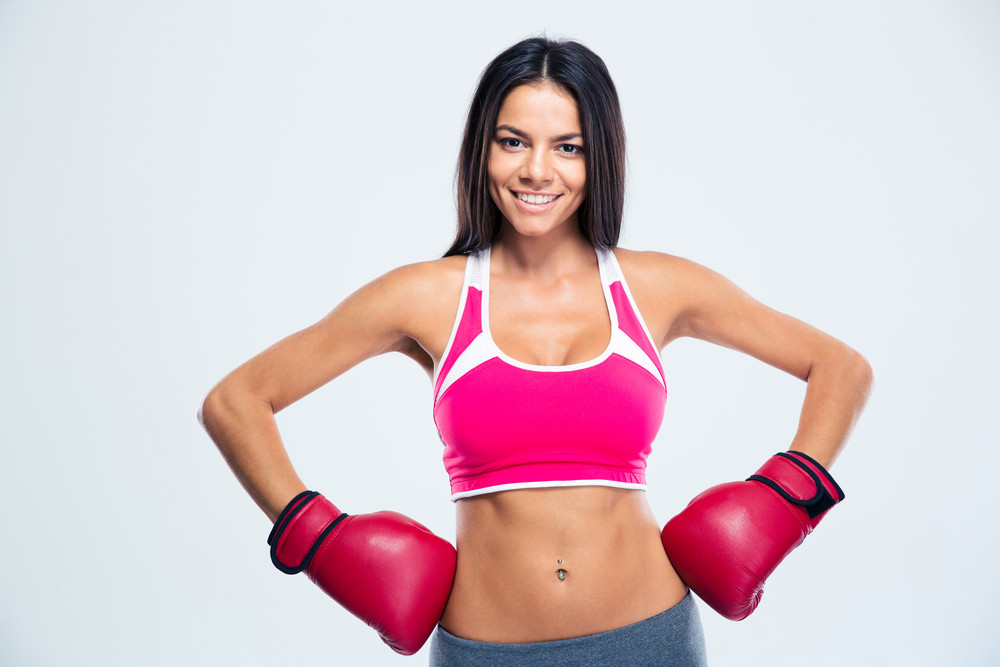 Smiling fitness woman in boxing gloves over gray background. Looking at camera