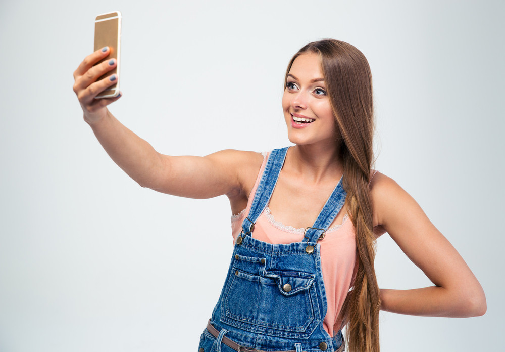 Smiling girl making selfie photo on smartphone