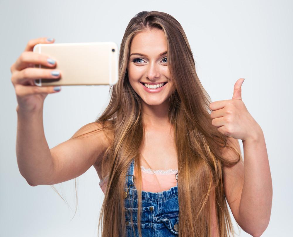 Smiling girl making selfie photo