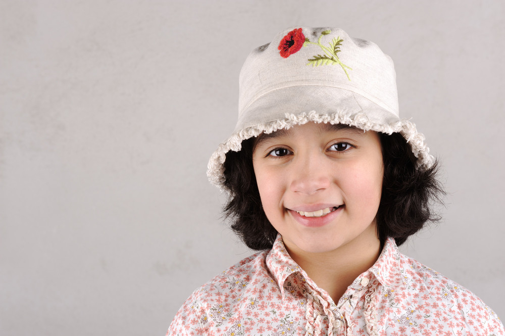 Smiling girl showing teeth wearing a  hat with red flower