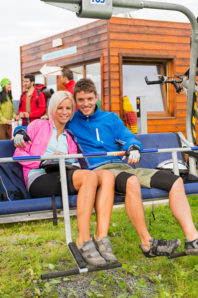 Smiling hugging couple sitting and waiting on chair-lift