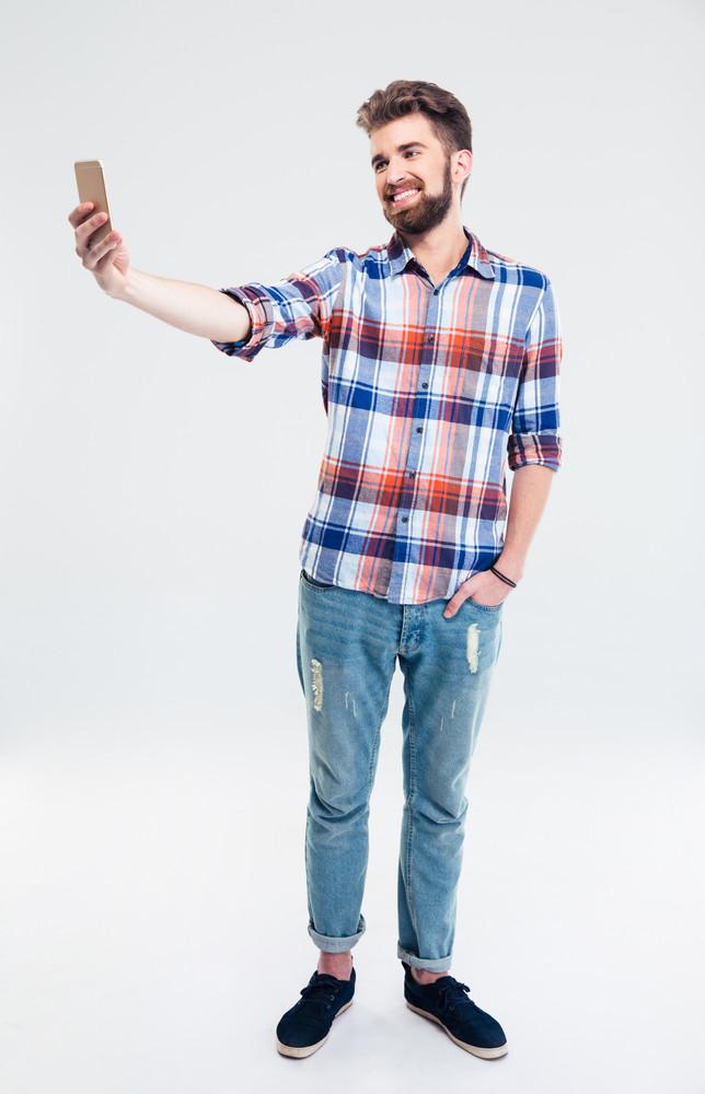 Smiling man making selfie photo on smartphone