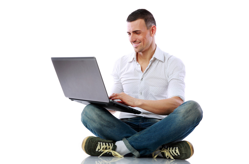 Smiling man sitting at the floor with laptop over white background