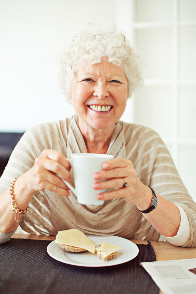Smiling old lady having her breakfast at home