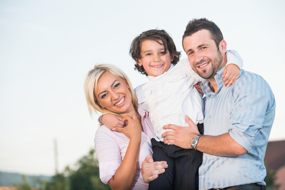Smiling parents posing with a happy child