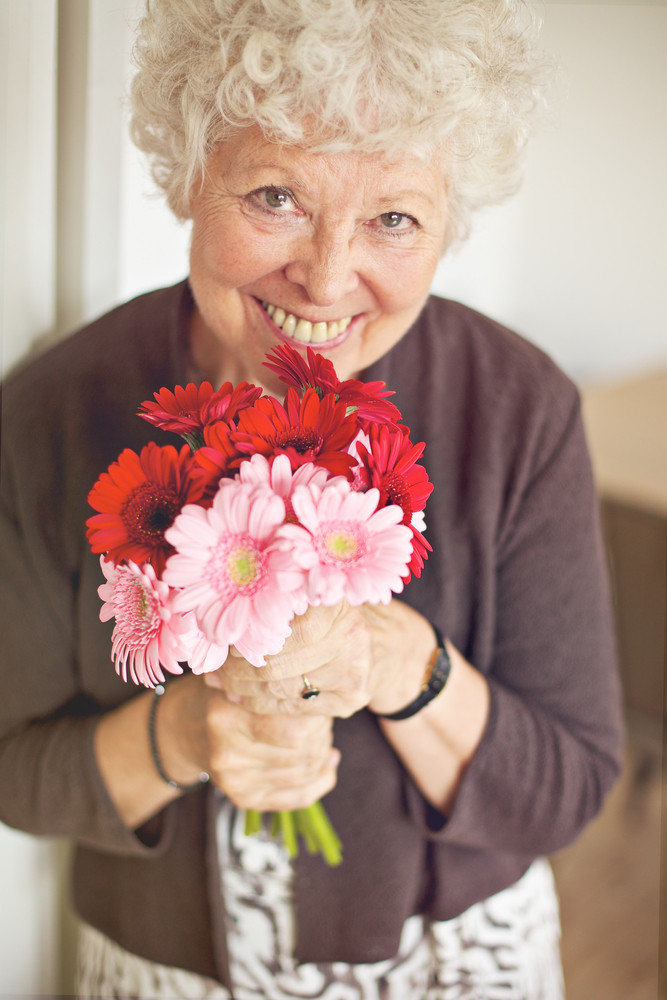 Smiling senior woman holding a bouquet of flowers
