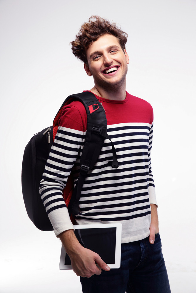 Smiling student with backpack and tablet computer over gray background