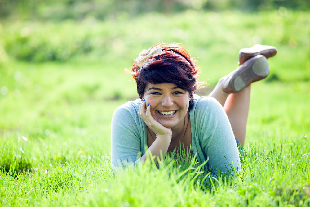 Smiling teenage girl laying in a green grassy field. Shallow depth of field.