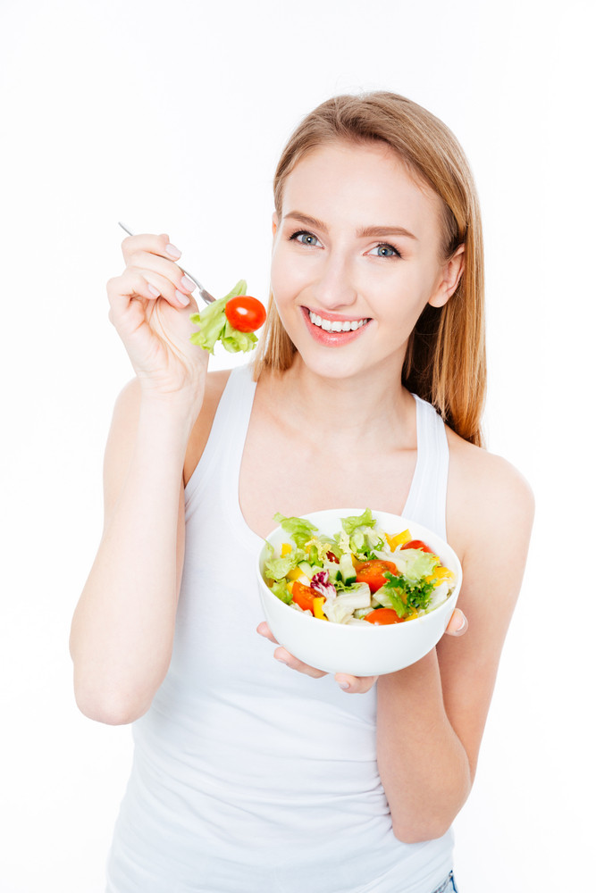 Smiling woman eating salad isolated on a white background