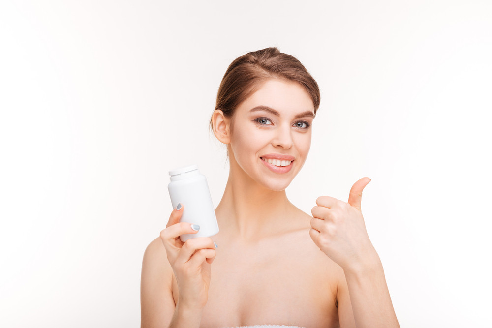 Smiling woman holding bottle with pills and showing thumb up isolated on a white background