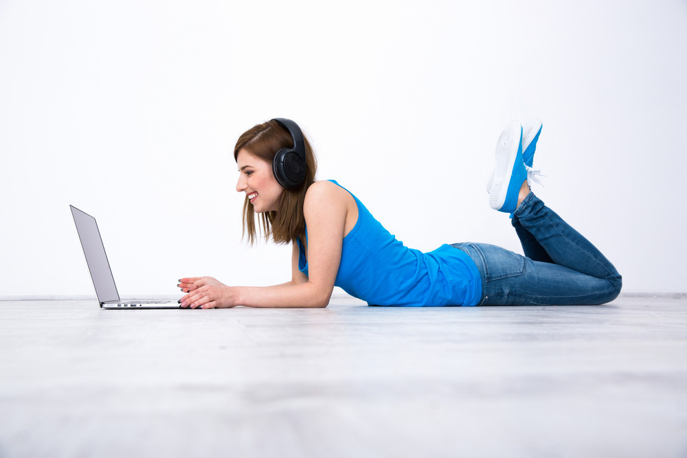 Smiling woman wearing headphones lying on the floor with laptop