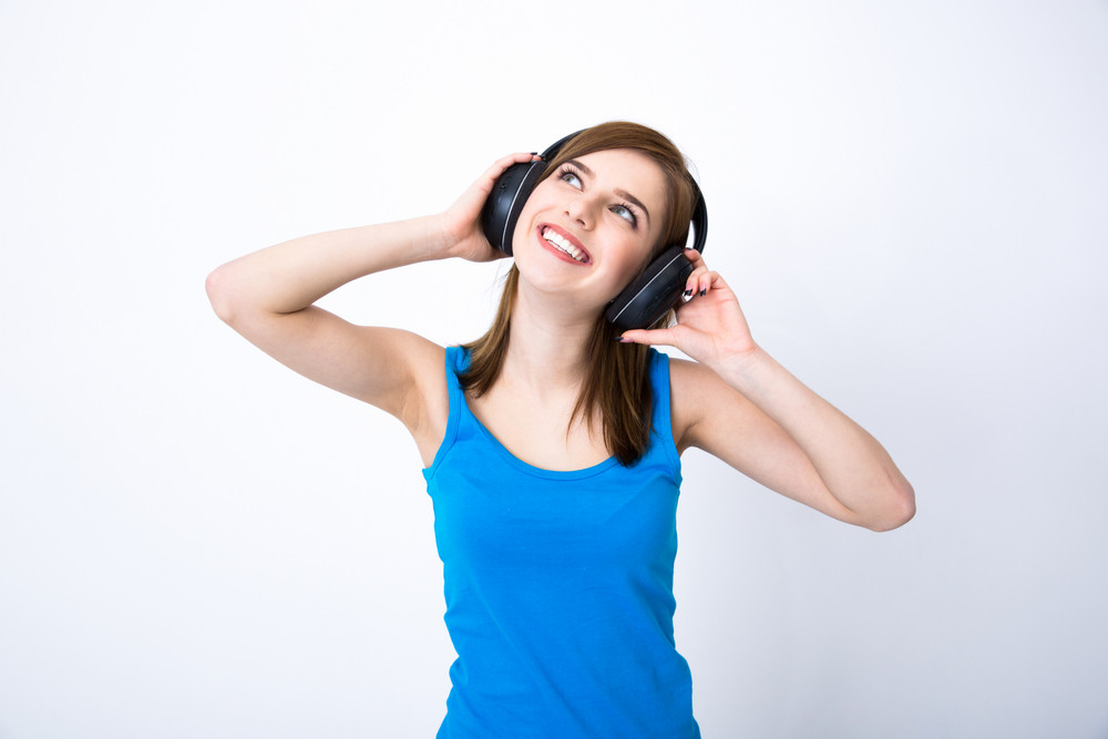 Smiling woman with headphones listening music and looking up