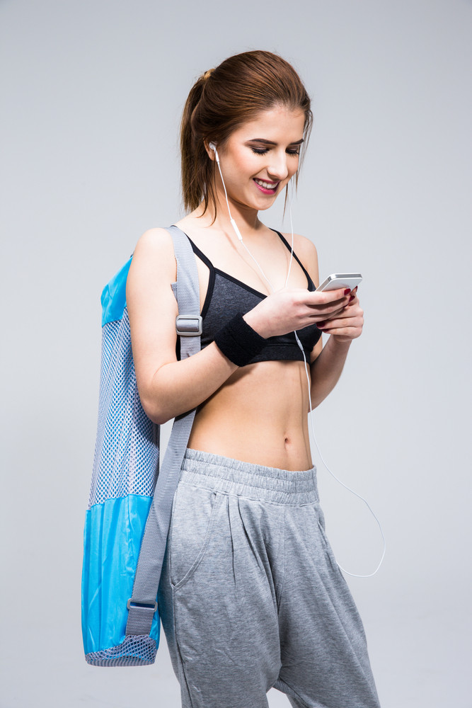 Smiling woman with yoga mat using smartphone over gray background
