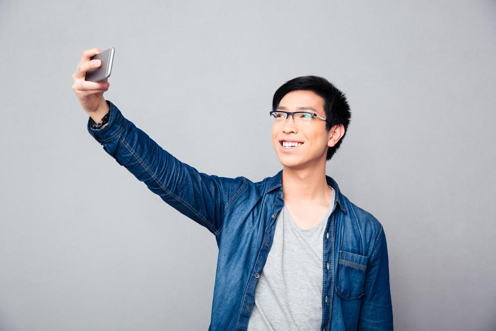 Smiling young asian man making selfie photo
