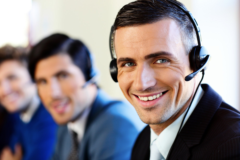 Smiling young businesspeople and colleagues in a call center office