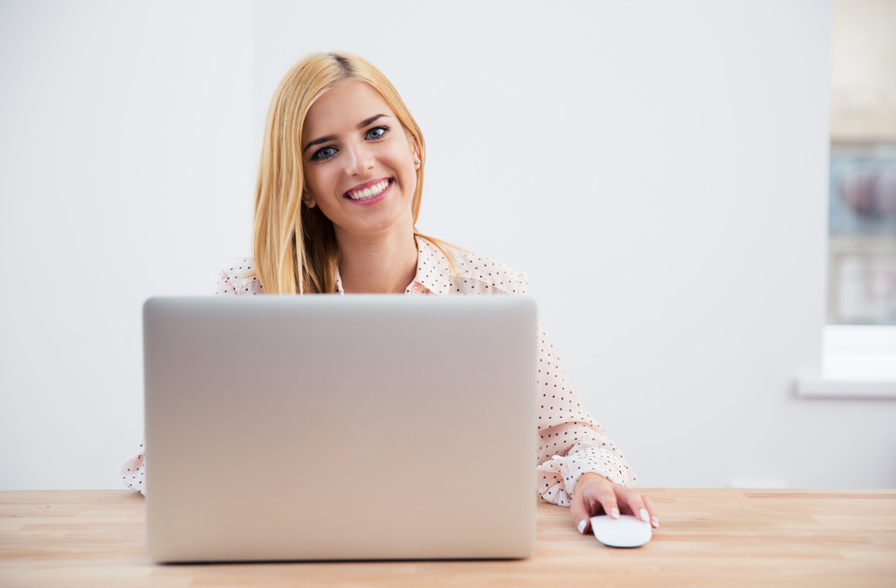Smiling young businesswoman using laptop