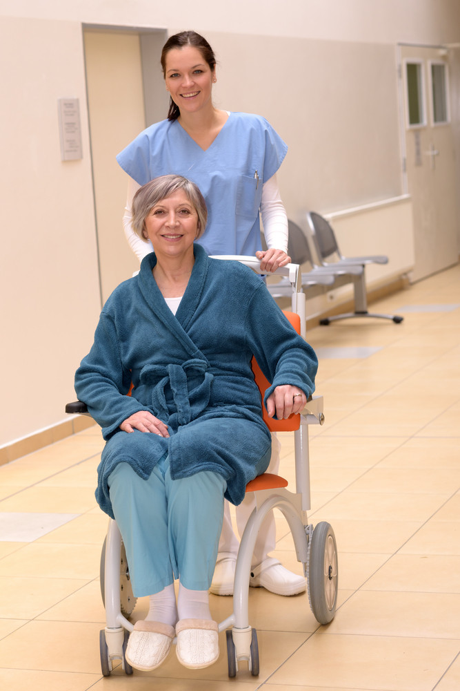 Smiling young female nurse in hospital pushing senior patient in wheelchair in hospital