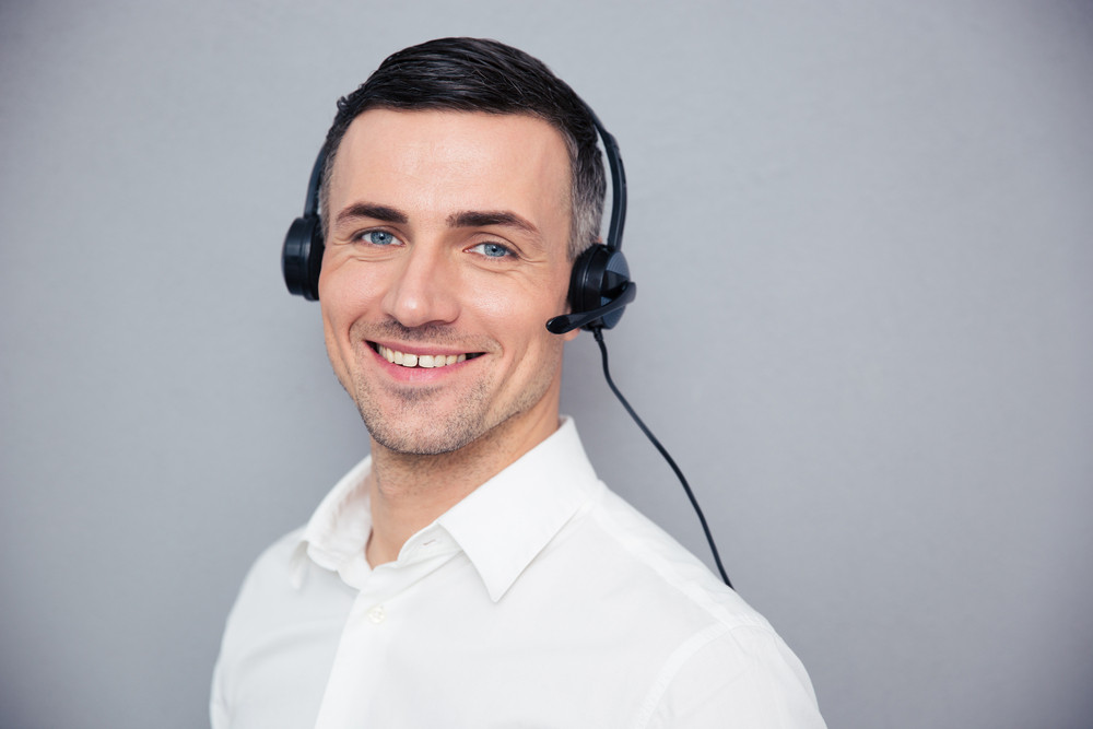 Smiling young male operator in headphones