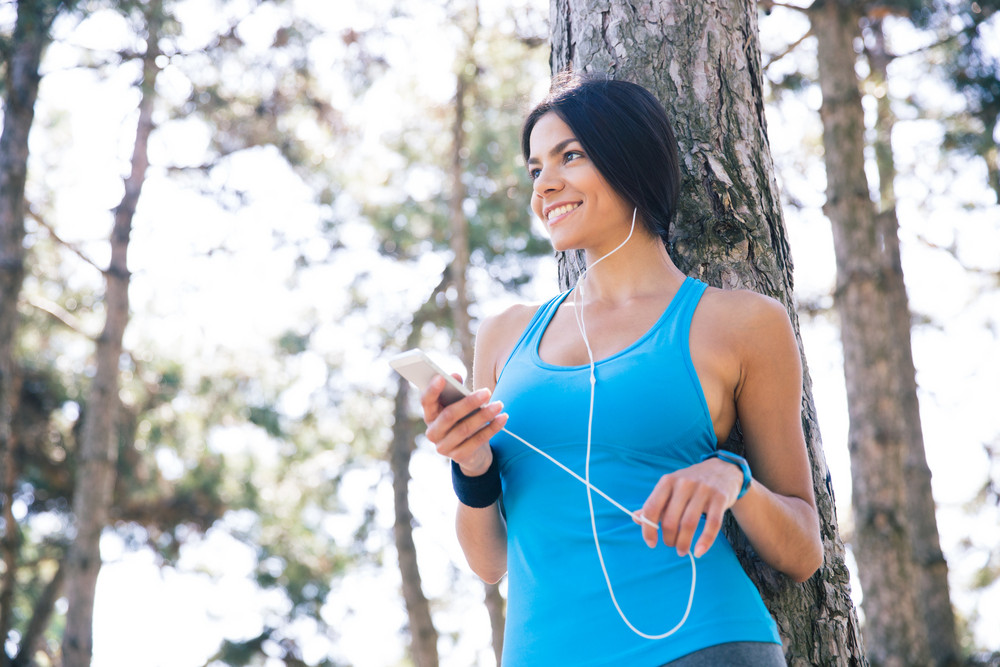 Sporty woman holding smartphone with headphones outdoors