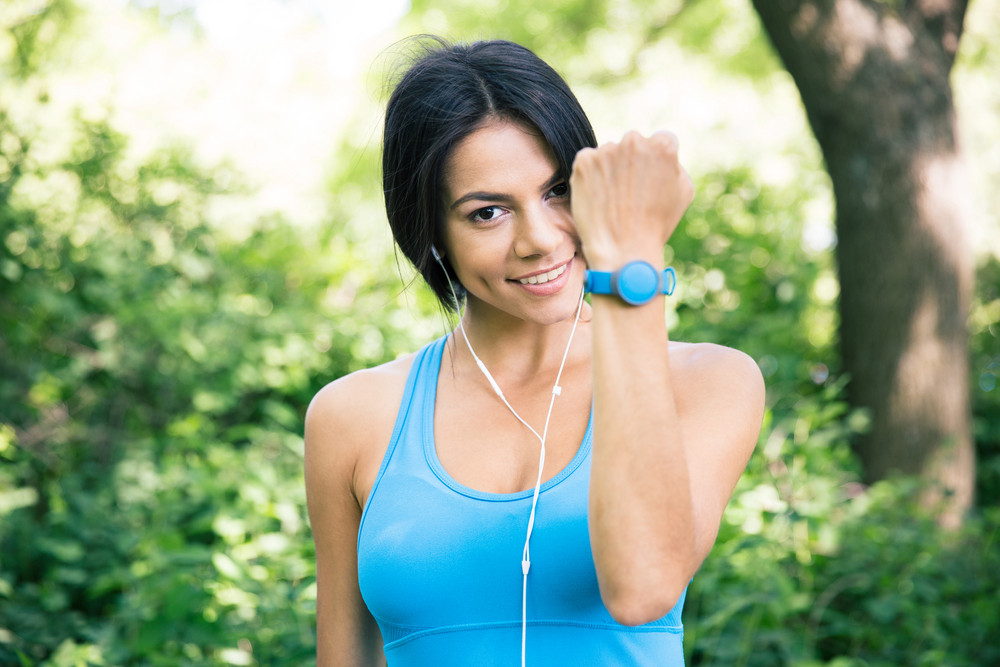 Sporty woman showing activity tracker on hand