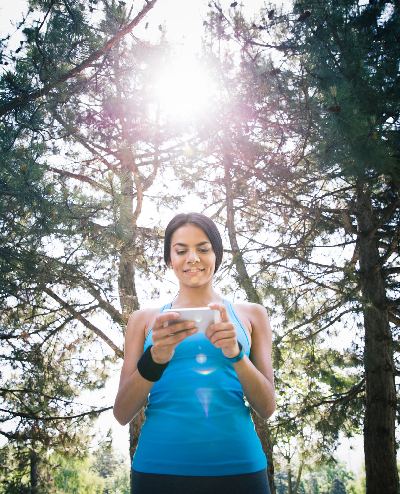 Sporty woman using smartphone outdoors