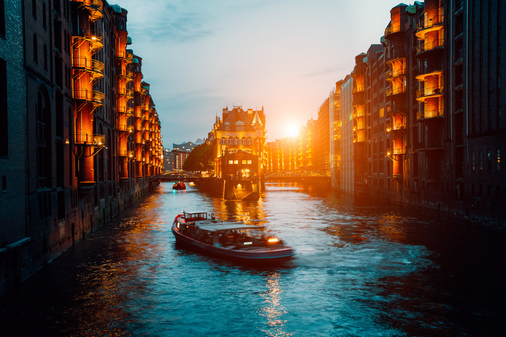 A colorfully illuminated boat cruising on the Wandrahmsfleet at night. The Warehouse District in Hamburg, Germany. The district located within the HafenCity quarter
