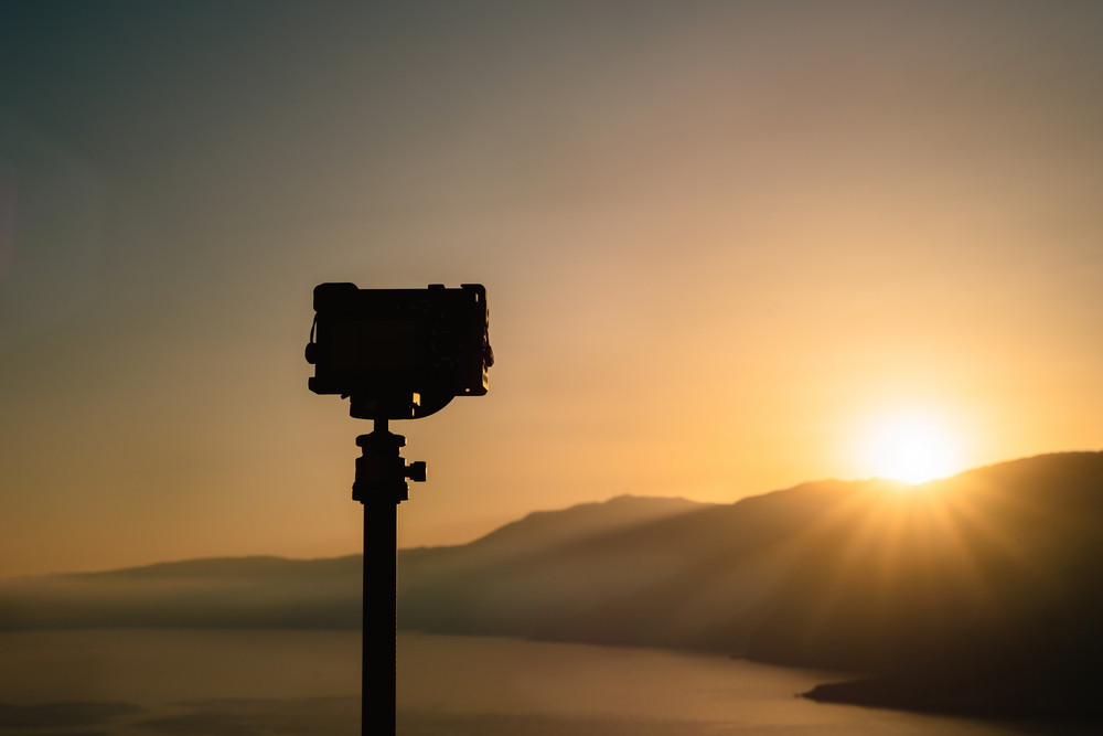 A travel image of a camera shooting sunrise on top of a hill In the distance, amazing sunrise and outline of a mountain. Calm sea below, greek island