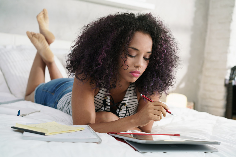 African american college student doing schoolwork on bed at home. Young black woman preparing school test in bedroom, studying with laptop