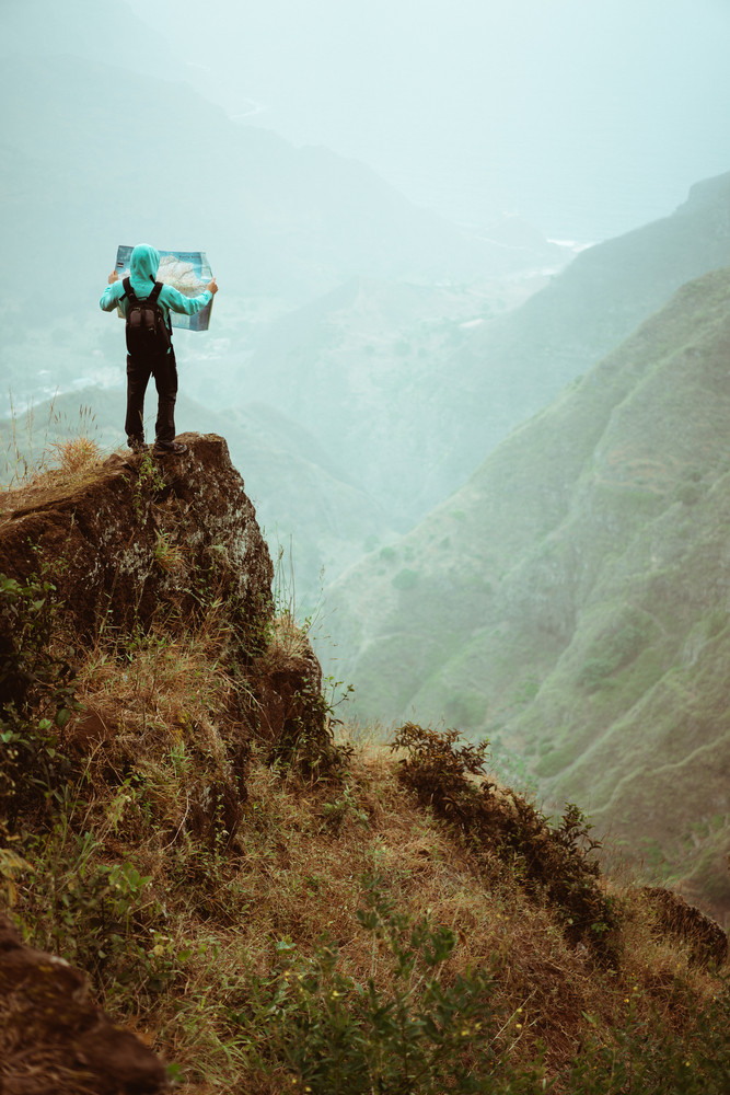Alone hiker with map of the island staying on a rocky ledge in front of a gorgeous panorama view of high mountain ranges and lush green valley. Santo Antao Cape Verde