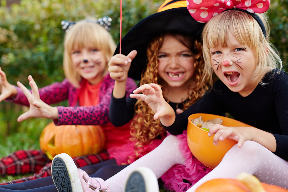 Angry girls with Halloween treats in plastic pumpkins