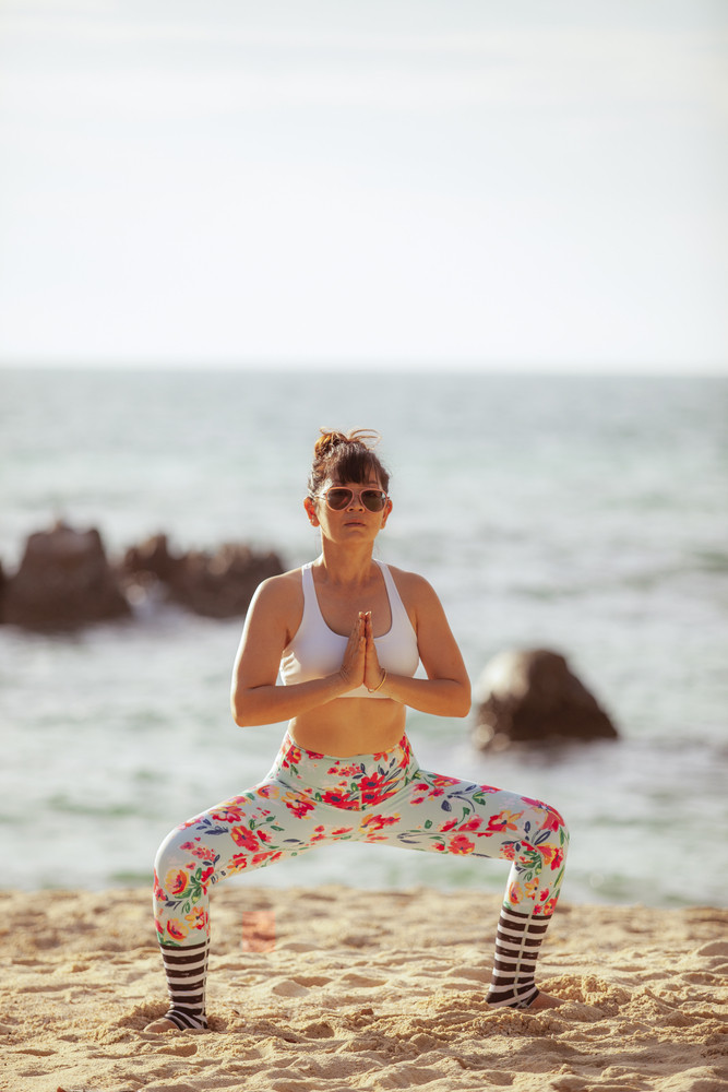 asian woman playing yoga pose on sea beach