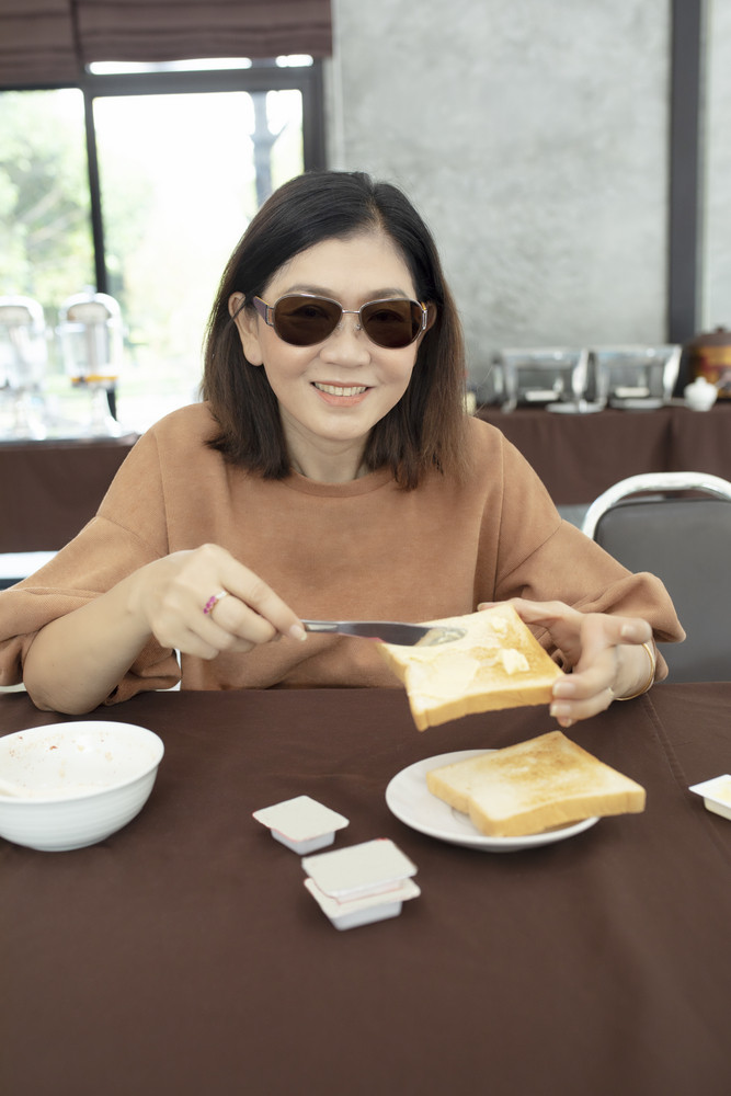 asian woman toothy smiling face with butter and bread in hand