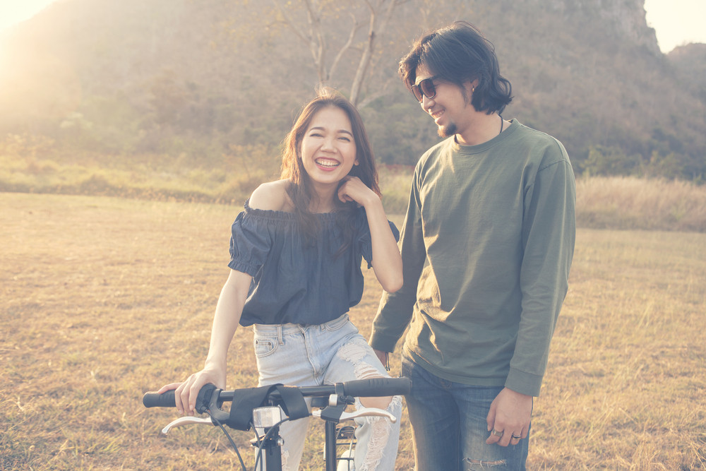 asian younger man and woman laughing and  relaxing outdoor