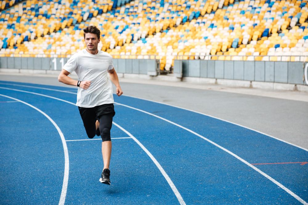 Athlete man running on a racetrack at a stadium