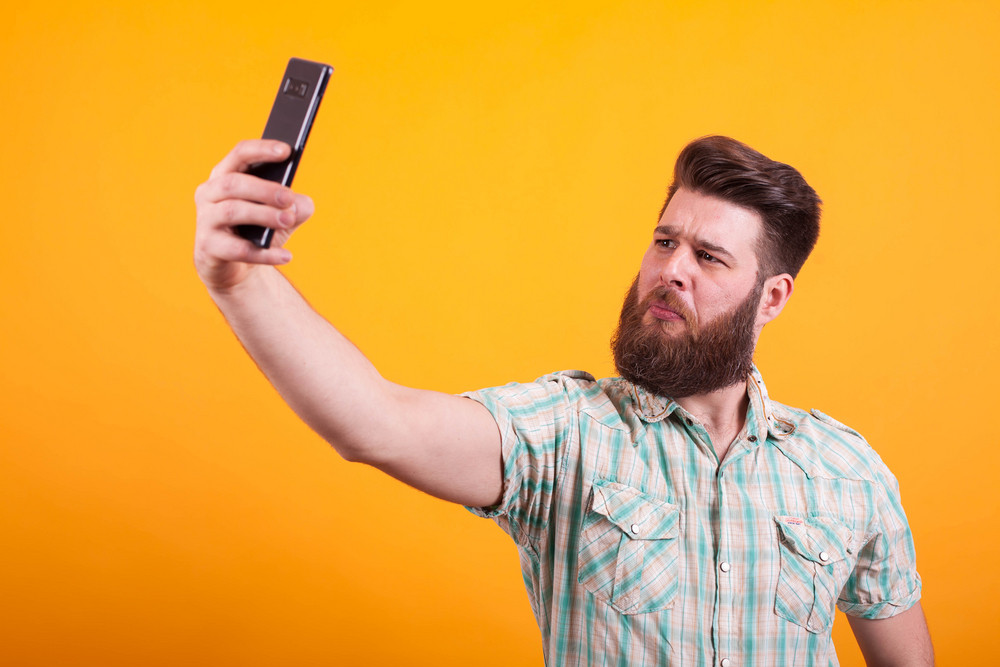 Attractice bearded man in shirt taking a selfie over yellow background. Modern technology. Stylish beard. Hipster man.