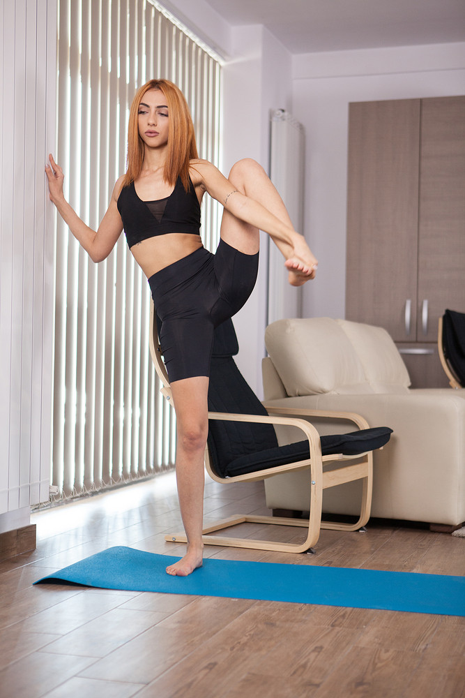Attractive girl doing great stretching home training. Great flexibility training.