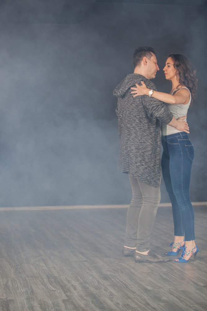 Attractive young man dancing with his girlfriend in dancing class. Beautiful couple.
