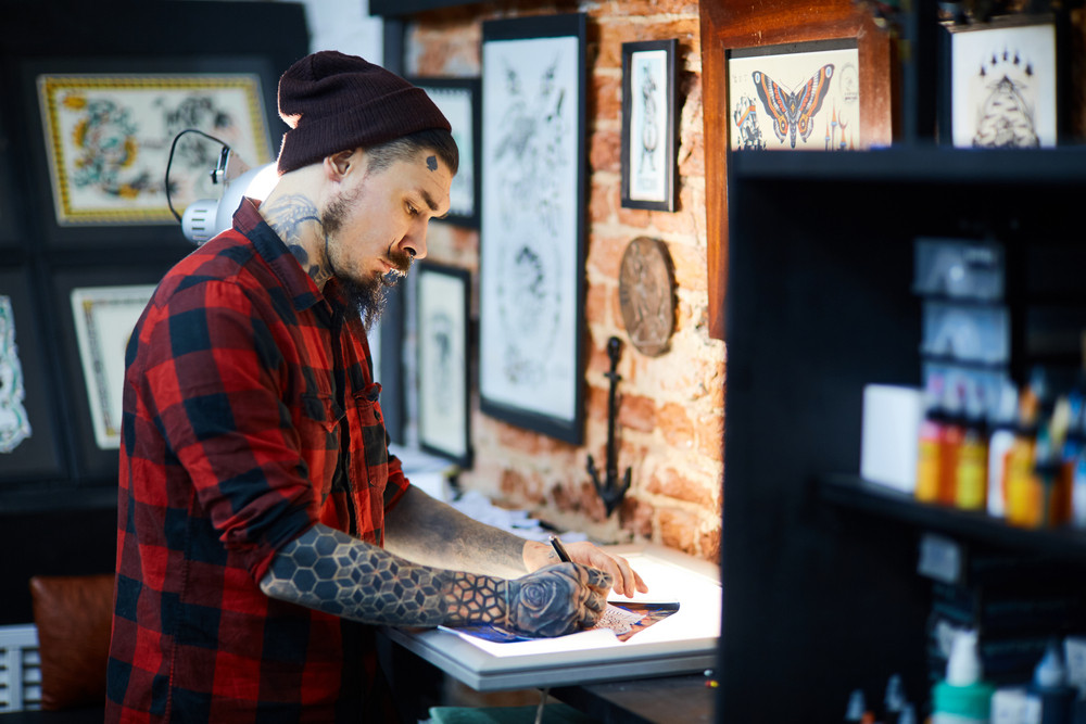 Bearded man in beanie-cap and shirt drawing picture of creative ornament in tattoo-salon