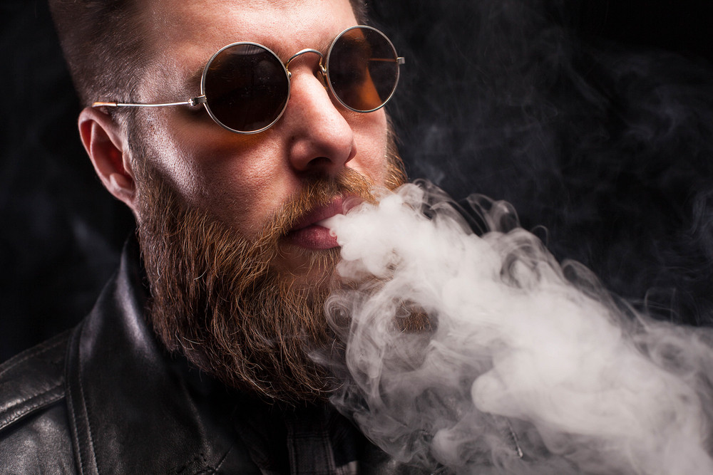 Bearded man in leather jacket and brown sunglasses over black background. Rocker beard. Serious expression.