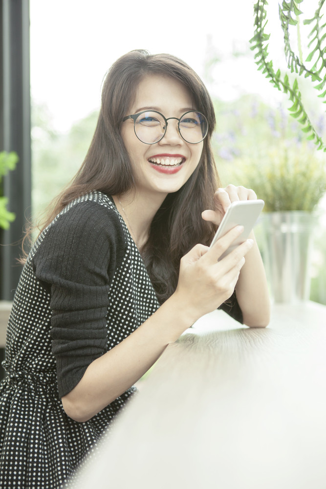 beautiful asian woman laughing face happiness emotion with smart phone in hand
