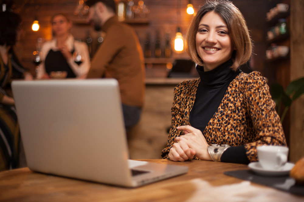 Beautiful businesswoman working on laptop in a coffe shop and smiling to the camera. Experienced freelancer