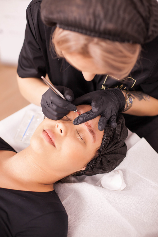 Beautiful in a beauty salon for her eyebrow tattoo removal. Modern treatment. Skin care. Hygiene procedure.
