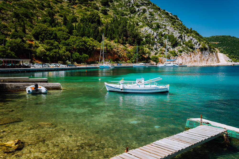 Beautiful tranquil sunny scenery of lovely greek harbor, blue sea with crystal clear water. Summer tourism vacation holidays boat trip, Greece