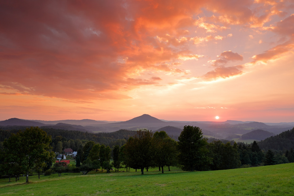 Beautiful twilight sunset landscape. Evening in hills with villages. Sun with ping and orange sky. Evening sun during sunset in Czech national Park Ceske Svycarsko, Bohemian Switzerland. Green meadow.