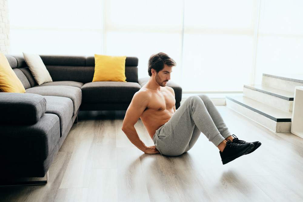 Beautiful young Hispanic man training at home, athlete exercising for wellness and healthy lifestyle in domestic gym, doing seated knee tucks on the floor in his living room