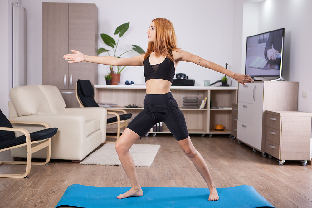Beautiful young woman staying in Warrior II yoga pose. Home posture training.