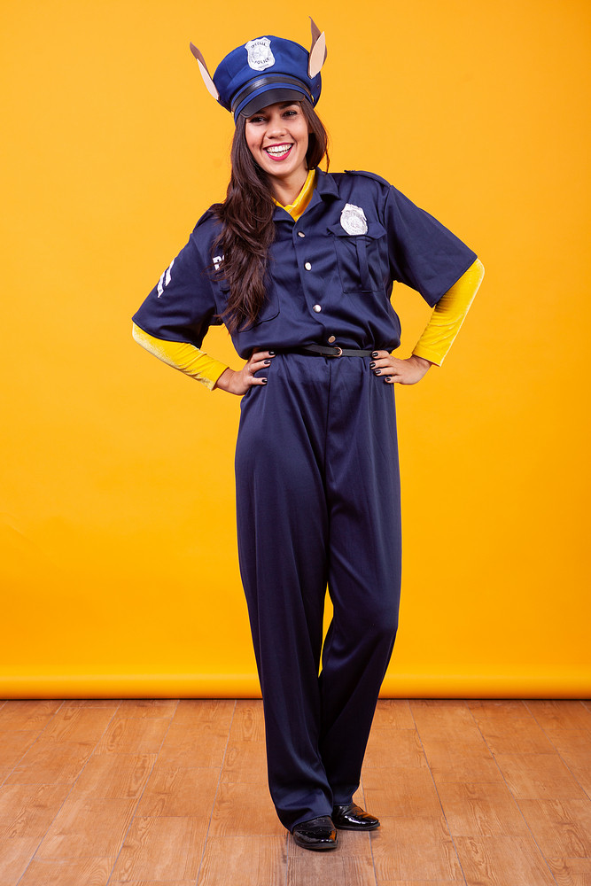 Attractive Beautiful Young Woman Wearing Police Costume Over Yellow Background. Having  Fun.